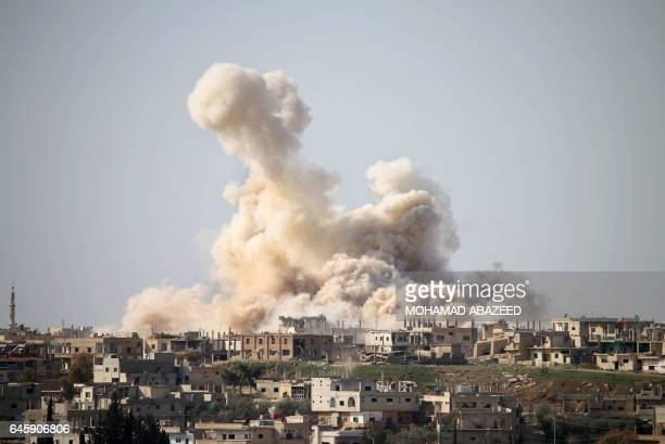 Smoke billows following reported air strikes on a rebelheld area in the southern city of Daraa on February 27 2017 Daraa province the cradle of the...
