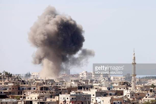 Smoke billows following reported air strikes on a rebelheld area in the southern Syrian city of Daraa on April 4 2017 / AFP PHOTO / Mohamad ABAZEED