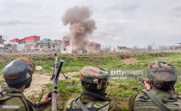 Smoke billows from a building as Indian army soldiers look towards it after they stormed it during a heavy exchange of fire between suspected rebels...