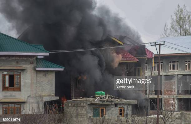 Smoke billows from a building during a heavy exchange of fire between militants and Indian government forces during a gun battle between militants...