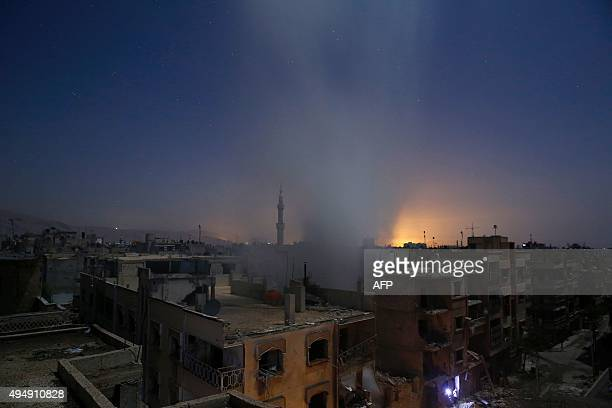 Smoke billows from a building early on October 30 following reported shelling by Syrian government forces in the rebelcontrolled area of Douma east...
