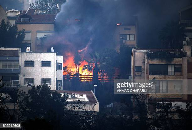 Smoke billows from a house as a fire rages in the northern Israeli port city of Haifa on November 24 2016 Hundreds of Israelis fled their homes on...