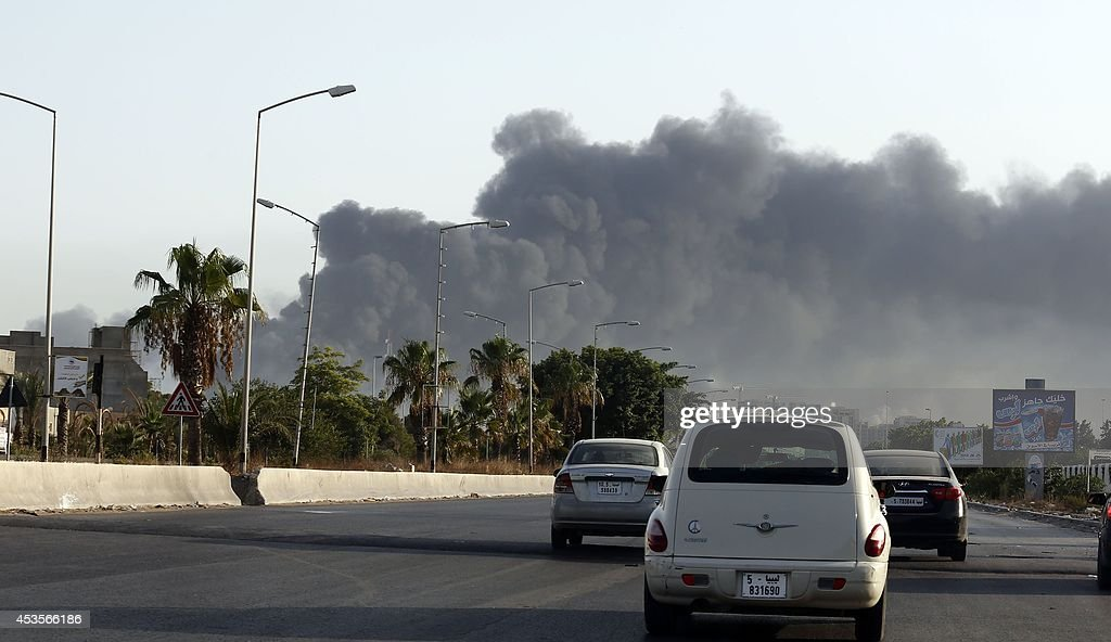 Smoke billows from a petrol depot set ablaze during clashes between rival militias near the Tripoli's international airport on the outskirts of the...