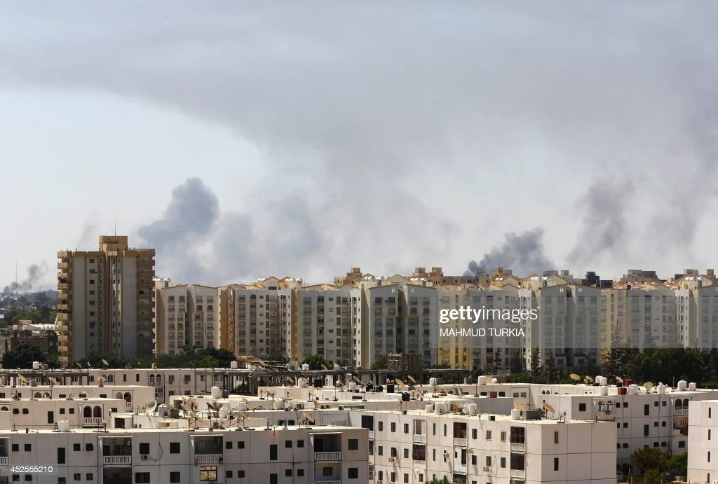 Smoke billows from a road leading to Tripoli's international airport as fighting between rival factions around the capital's airport continued on the...