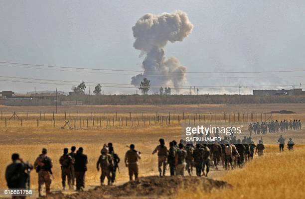 TOPSHOT Smoke billows from an area near the Iraqi town of Nawaran some 10km north east of Mosul as Iraqi Kurdish Peshmerga fighters march down a dirt...