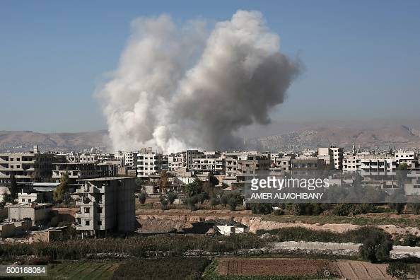 Smoke billows from buildings following a reported air strike in Damascus' rebelheld suburb of Zamalka on December 6 2015 AFP PHOTO / AMER ALMOHIBANY...