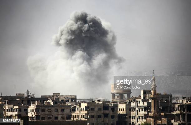 TOPSHOT Smoke billows from buildings following a reported air strike on Ain Tarma in the Eastern Ghouta area a rebel stronghold east of the Syrian...