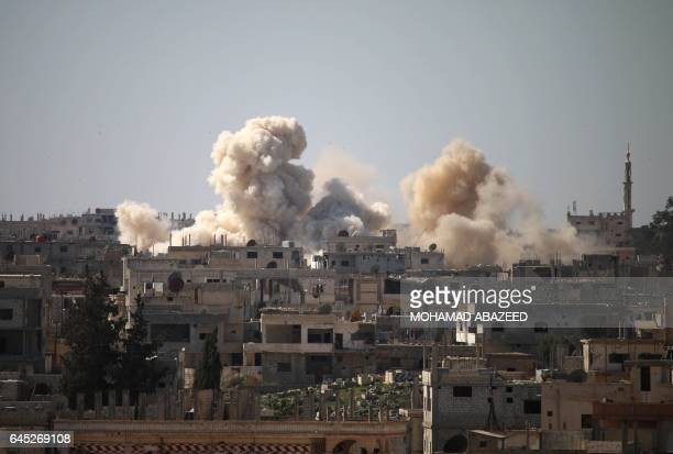 Smoke billows from buildings following reported air strikes on a rebelheld area in the southern city of Daraa on February 25 2017 / AFP / MOHAMAD...
