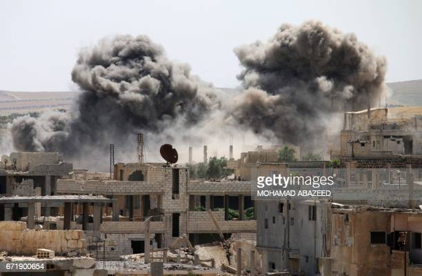 Smoke billows from buildings in a rebelheld neighbourhood of Daraa following reported air strikes on April 23 2017 / AFP PHOTO / Mohamad ABAZEED