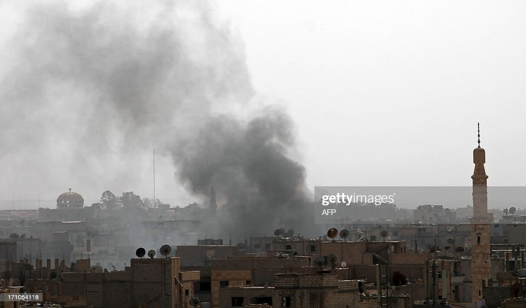 Smoke billows from buildings in the Jubaila neighbourhood of Syria's northeastern city of Deir Ezzor following an airstrike by government forces on June 21, 2013. Syria's rebels have received new types of weapons that could 'change the course of the battle,' a rebel spokesman said, as troops tried to oust opposition fighters from a Damascus district. AFP PHOTO / AHMAD ABOUD
