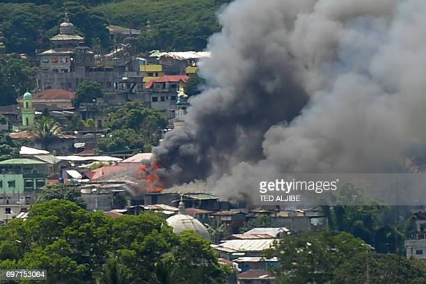 Smoke billows from burning buildings in Marawi on the southern island of Mindanao on June 18 after Philippine Airforce planes pounded Islamist...