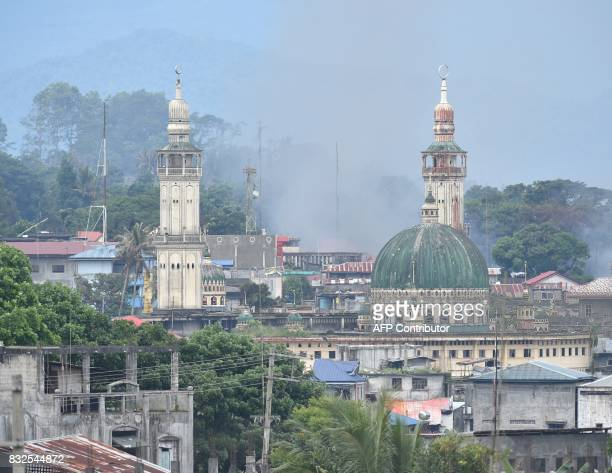 Smoke billows from burning houses after Philippine airforce attack plane dropped bomb on Muslim militants position during an aerial bombinmg in...