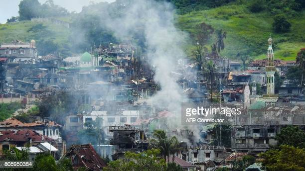 Smoke billows from burning houses as fighting between government troops and Islamist militants continues in Marawi on the southern island of Mindanao...