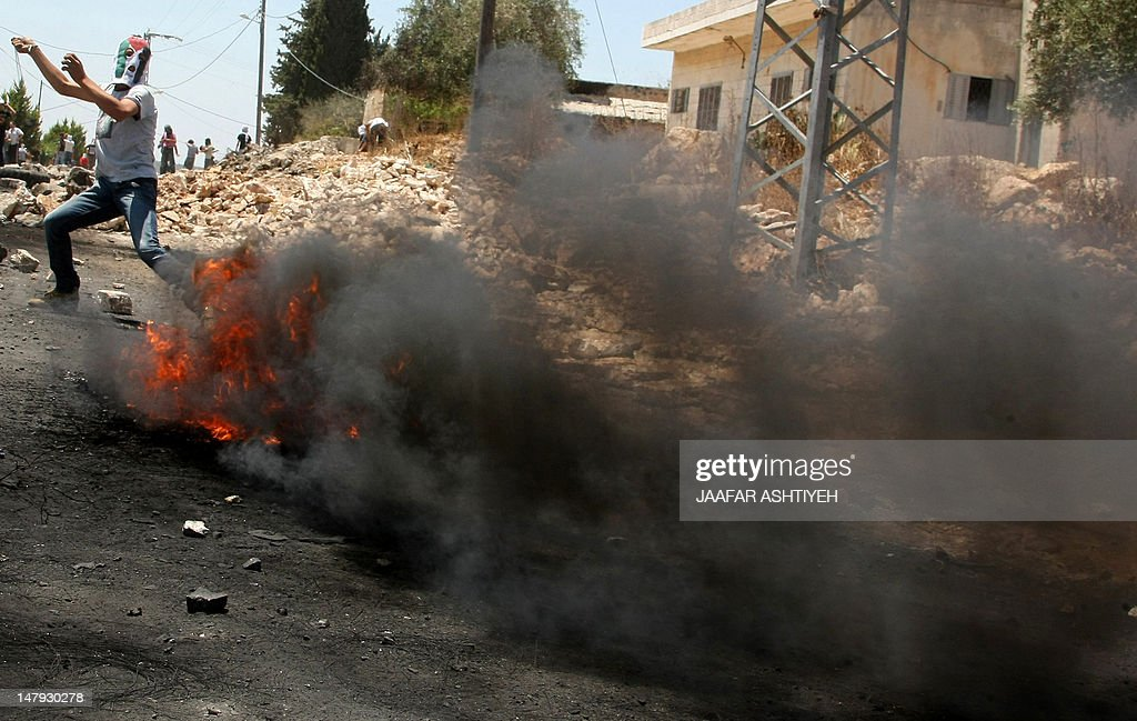 Smoke billows from burning tyres as a Palestinian demonstrator uses a slingshot to hurl stones towards Israeli troops during a protest against the expropriation of Palestinian land by Israel in the West Bank village of Kafr Qaddum near Nablus on July 6, 2012.