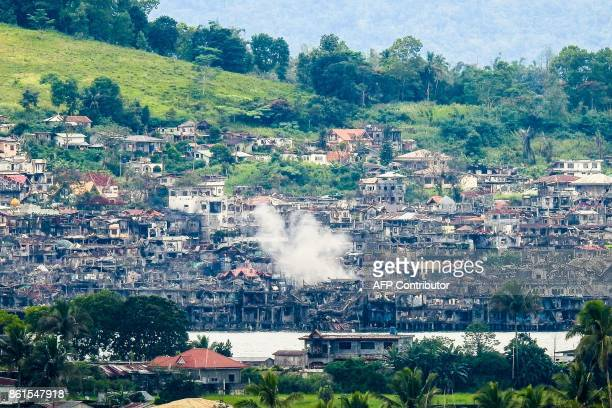 Smoke billows from destroyed buildings after government troops fired mortars at an Islamic State position in Marawi on the southern island of...