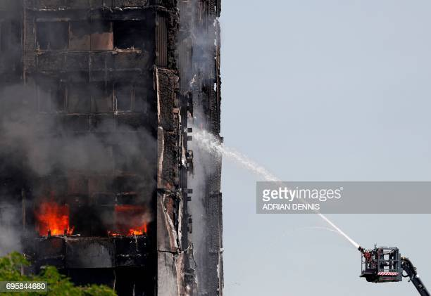 TOPSHOT Smoke billows from Grenfell Tower as firefighters attempt to control a blaze at a residential block of flats on June 14 2017 in west London...