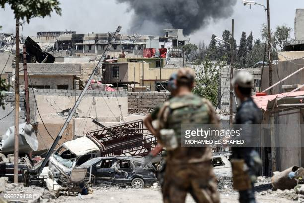 TOPSHOT Smoke billows from Mosul's western AlShifa district on June 15 during the ongoing offensive by Iraqi forces to retake the city from Islamic...