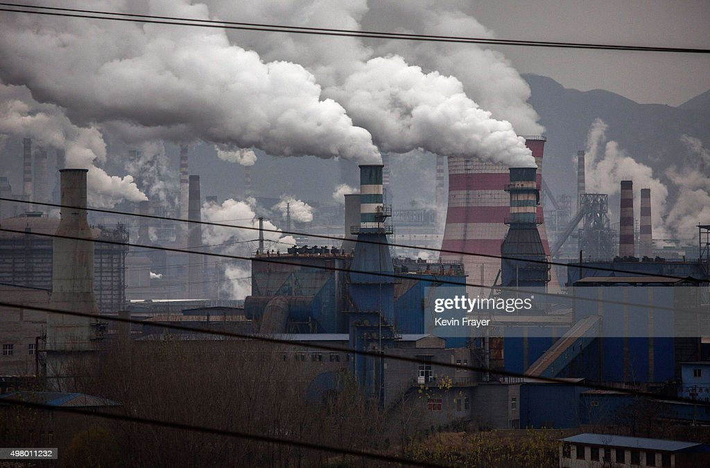 Smoke billows from smokestacks and a coal fired generator at a steel factory on November 19 2015 in the industrial province of Hebei China China's...