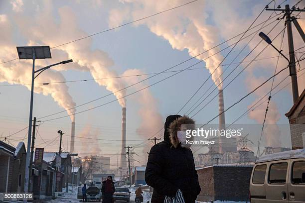 Smoke billows from stacks as a Chinese woman wears as mask while walking in a neighborhood next to a coal fired power plant on November 26 2015 in...