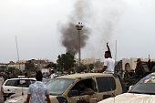 Smoke billows from the site of shelling by antigovernemnt forces as Libyans attended a protest against a national unity government proposal by United...