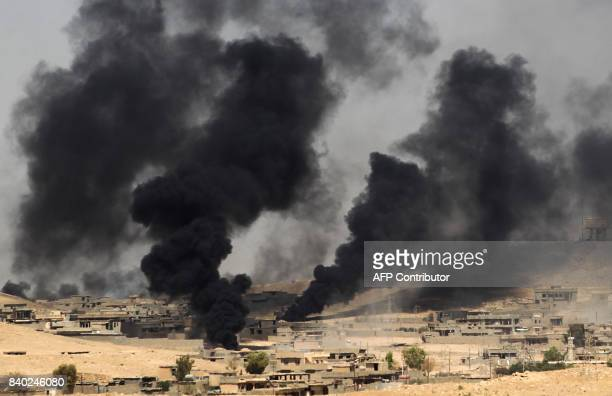 TOPSHOT Smoke billows from the village of alAyadieh near Qubuq north of Tal Afar as Iraqi forces advance during the ongoing operation to retake the...