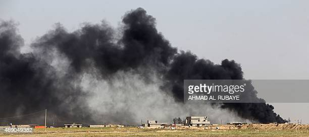 Smoke billows from what is believed to be an oil field which was set alight by Islamic State group militants in the Mkeishifa area south of the...