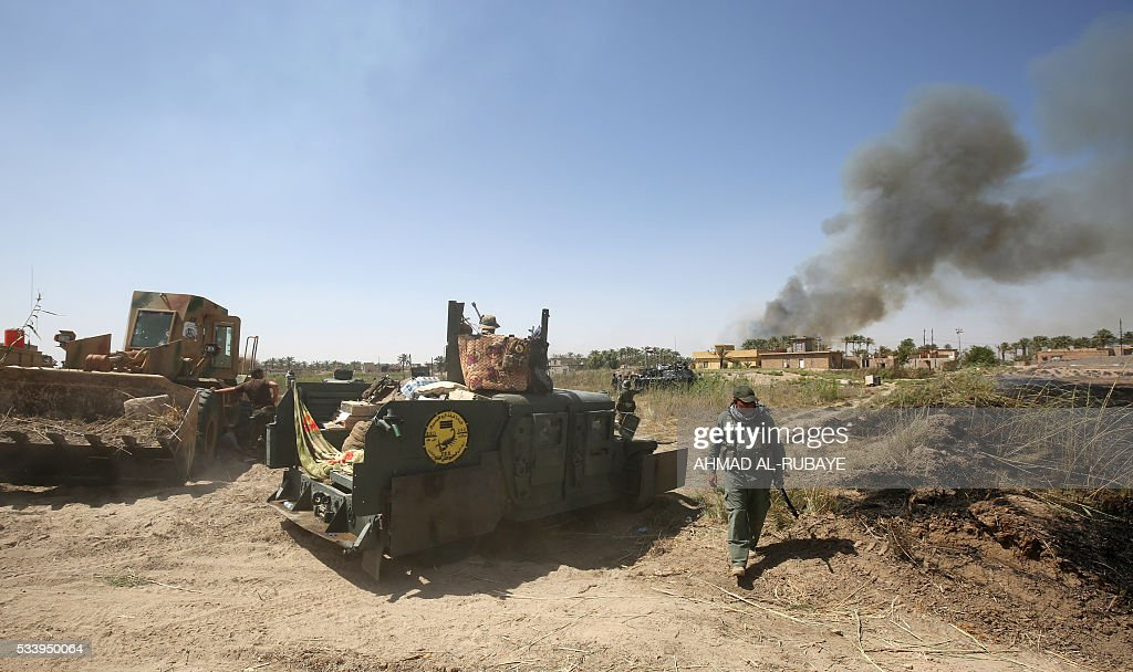 Smoke billows in al-Shahabi village, east of Fallujah, on May 24, 2016, as Iraqi pro-government fighters take part in a major assault to retake the city from Islamic State (IS) group. Iraqi forces cleared areas around Fallujah on May 24 after launching an assault to retake the city, tightening their siege on Islamic State group fighters. With the jihadists surrounded and outnumbered, the recapture of their iconic bastion looked ultimately inevitable, especially after IS suffered a string of losses in recent months. / AFP / AHMAD