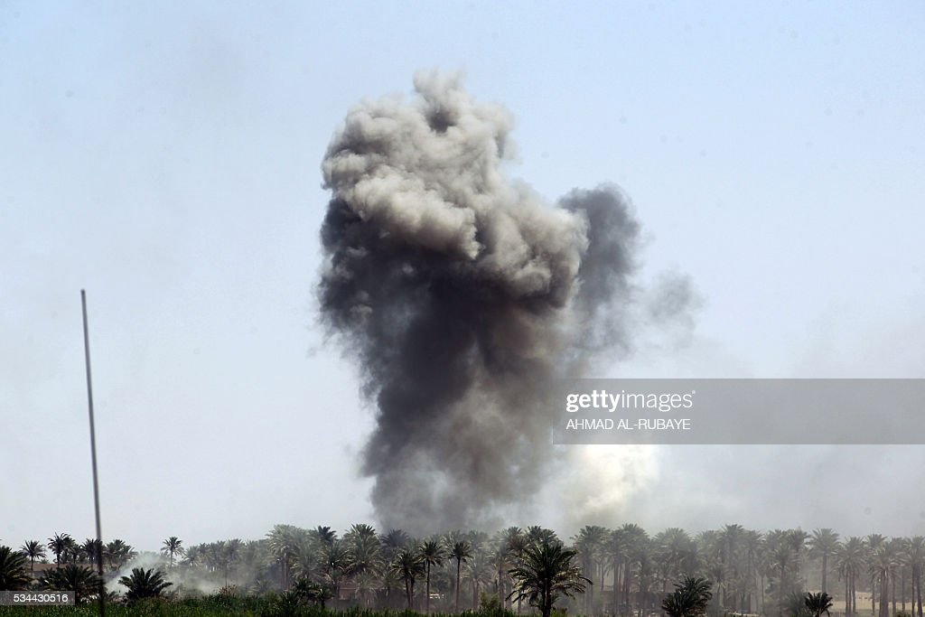 Smoke billows in the background as Iraqi government forces advance near al-Sejar village, north-east of Fallujah, on May 26, 2016, as they take part in a major assault to retake the city from the Islamic State (IS) group. Tens of thousands of security forces are deployed in the Fallujah area for an assault aimed at retaking the city from the Islamic State group. Fallujah, which lies only 50 kilometres (30 miles) west of Baghdad, has been out of government control since January 2014 and is one of only two remaining major Iraqi cities still in IS hands, the other being Mosul. / AFP / AHMAD