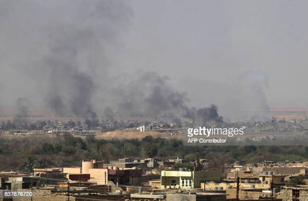 Smoke billows in the background as the Iraqi forces backed by Shiite fighters from the Popular Mobilization Forces advance inside alNour...