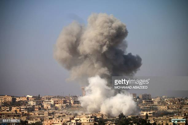 Smoke billows in the distance following reported air strikes on the southern Syrian city of Daraa on February 23 2017 / AFP / MOHAMAD ABAZEED