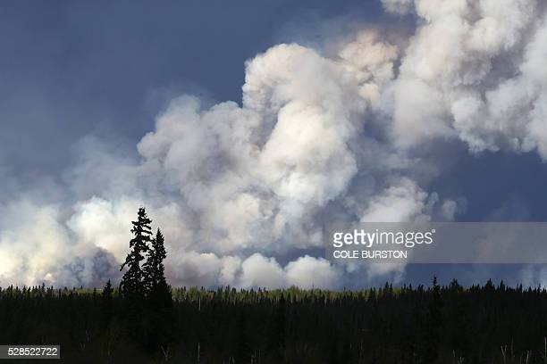 Smoke billows in the sky near Fort McMurray Alberta on May 5 2016 The Province of Alberta has issued a State of Emergency as more than 85000 hectares...