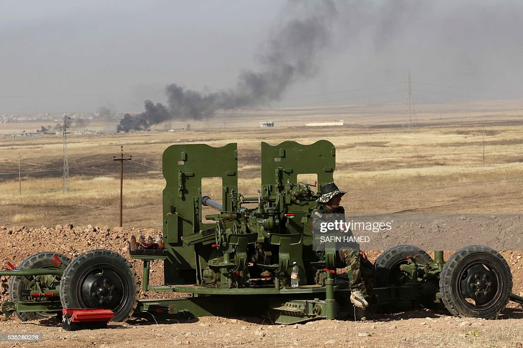 Smoke billows on the front line as an Iraqi Kurdish Peshmerga fighter holds a position near Hasan Sham village, some 45 kilometres east of the city of Mosul, during an operation aimed at retaking areas from the Islamic State group on May 29, 2016. The 'peshmerga-led ground offensive, backed by international coalition warplanes' started before dawn, the Kurdistan Region Security Council (KRSC) said. The fresh push against the jihadist organisation comes a week after Iraqi forces launched an operation against Fallujah, IS's only other major urban hub in Iraq. / AFP / SAFIN