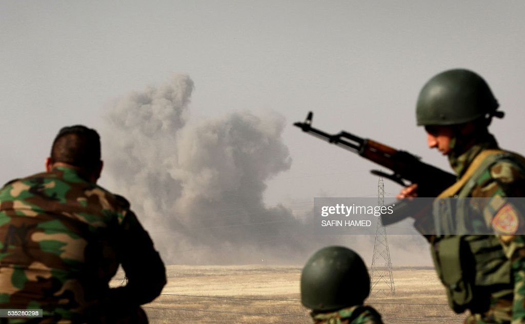 Smoke billows on the front line as Iraqi Kurdish Peshmerga fighters hold a position near Hasan Sham village, some 45 kilometres east of the city of Mosul, during an operation aimed at retaking areas from the Islamic State group on May 29, 2016. The 'peshmerga-led ground offensive, backed by international coalition warplanes' started before dawn, the Kurdistan Region Security Council (KRSC) said. The fresh push against the jihadist organisation comes a week after Iraqi forces launched an operation against Fallujah, IS's only other major urban hub in Iraq. / AFP / SAFIN