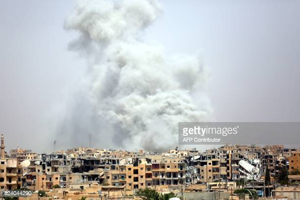 TOPSHOT Smoke billows out from Raqa following a coalition air strike on July 28 2017 The Syrian Democratic Forces a USbacked KurdishArab alliance has...