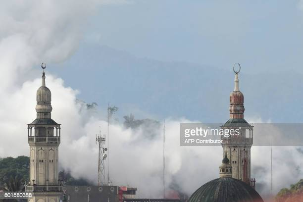 Smoke billows past minarets after an aerial bombing by the Philippine Air Force on militant Islamist positions in Marawi on the southern island of...