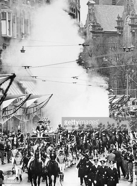 A smoke bomb explodes behind the coach carrying Princess Beatrix and her groom German diplomat Claus Von Amsberg during their wedding procession in...