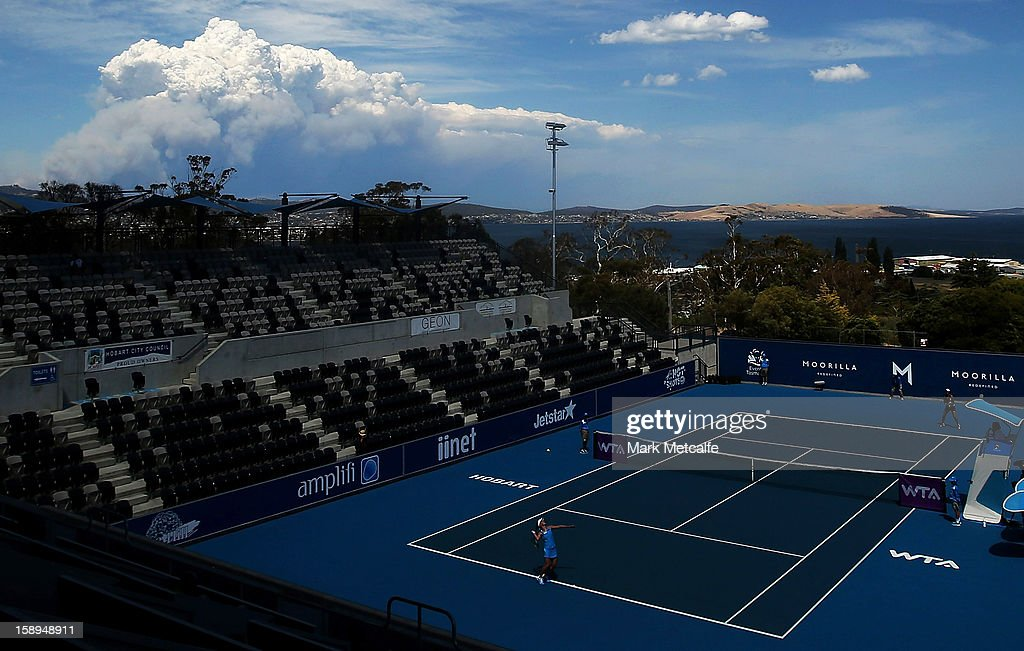 Smoke clouds from a nearby bushfire are seen as play continues on centre court during day one of the Hobart International at Domain Tennis Centre on January 4, 2013 in Hobart, Australia.