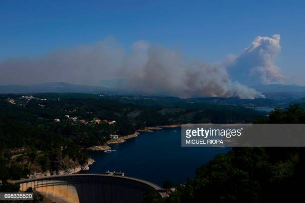 Smoke columns raise as wildfires burn on the background of the Cabril Dam close to Pedrogao Pequeno on June 20 2017 The huge forest fire that erupted...