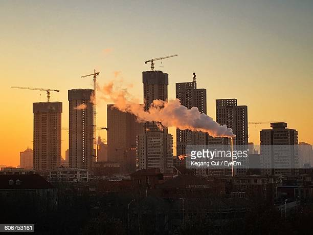 Smoke Coming Out From Factory Against Buildings In City At Sunset
