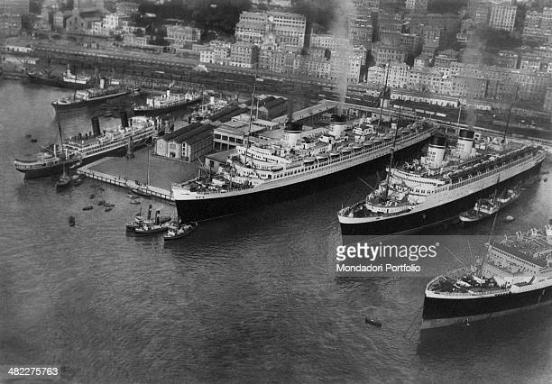 Smoke coming out from the funnel of some ships moored at the port Genoa 1930s