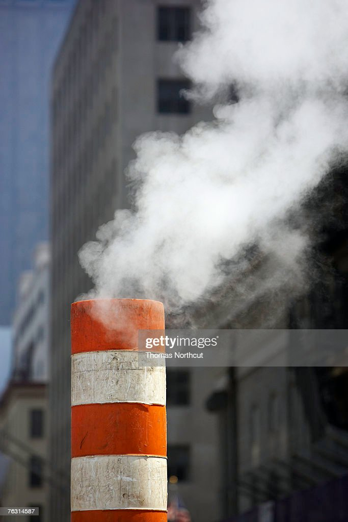 Smoke coming out of pipe used to release underground pressure : Stock Photo