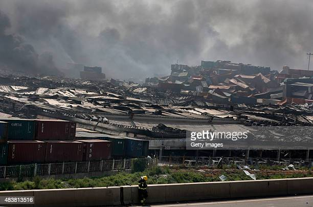 Smoke continues at the accident site after explosions from a warehouse on late Wednesday in Binhai New Area on August 13 2015 in Tianjin China At...