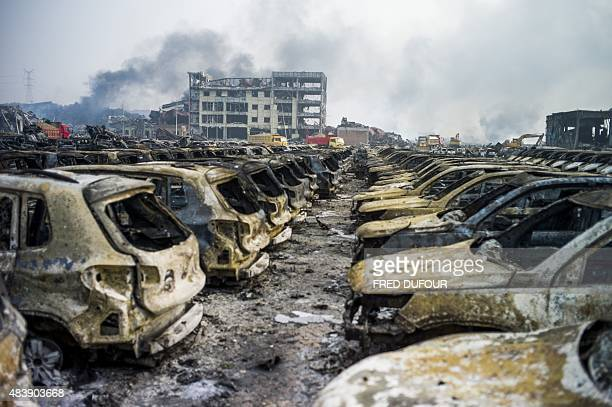 Smoke continues to billow from behind rows of burnt out Volkswagen cars the second morning after a series of explosions at a chemical warehouse hit...