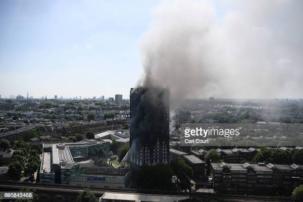 Smoke continues to rise from the burning 24 storey residential Grenfell Tower block in Latimer Road West London on June 14 2017 in London England The...
