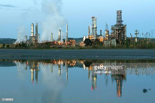 Smoke drifts away from a Shell Oil refinery April 1 2004 in Martinez California Analysts predict that OPEC's decision to cut its oil output target by...