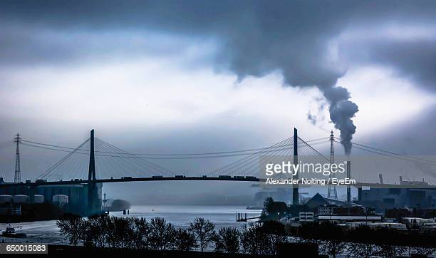 Smoke Emitting By Kohlbrandbrucke Over River Against Sky At Dusk