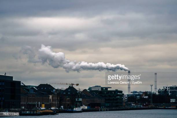 Smoke Emitting From Factory Against Cloudy Sky