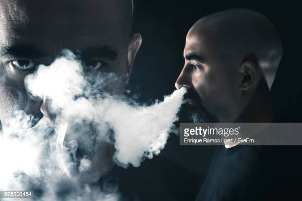 Smoke Emitting From Mature Man Nose While Standing By Friend Against Black Background
