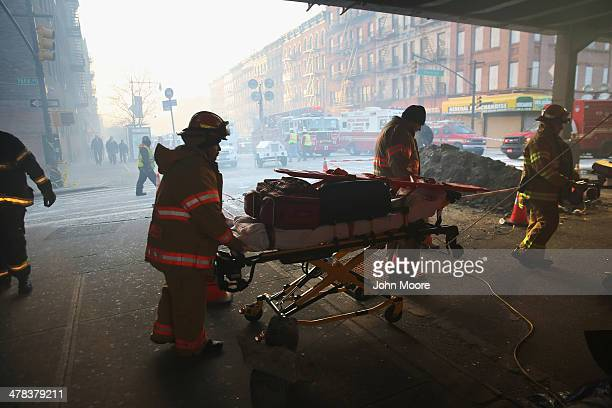 Smoke fills 116th street as a stretcher of paramedic equipment is wheeled near the site of an explosion in East Harlem on March 13 2014 in New York...