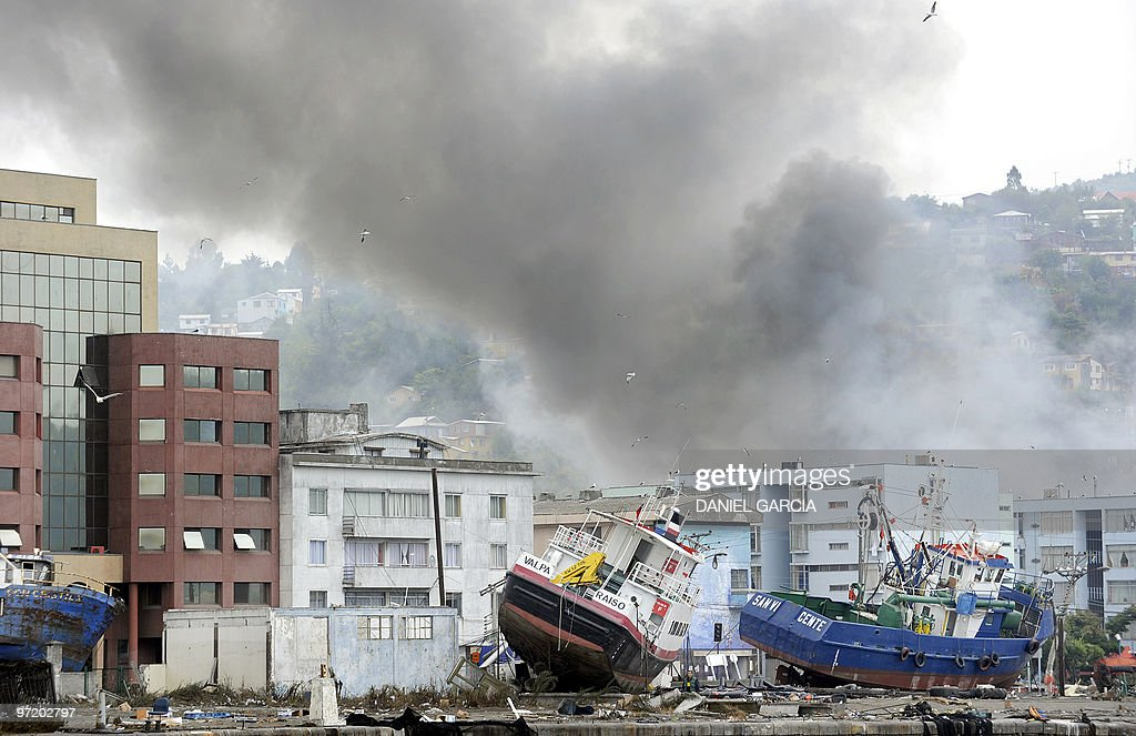 Smoke fills the air under buildings and boats that were taken ashore by a tsunami caused by a massive 88 magnitude earthquake in Talcahuano 20 kms...